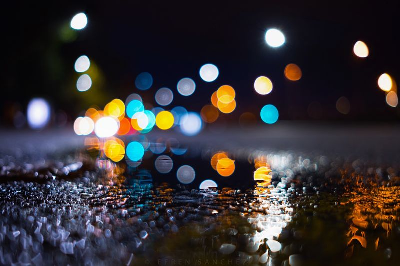 Defocused image of illuminated lights on wet road