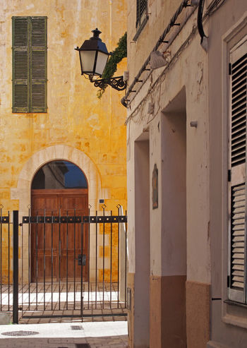 the corner of a sunlit street in ciutadella menorca with and old door behind a fence with shutters and a street lamp Architecture Built Structure Building Exterior Building Lighting Equipment Window Arch No People Day Street Light Street Residential District Electric Lamp Entrance Outdoors Door City Yellow Sunlight Nature City Tourism Ciutadella Corner Fence