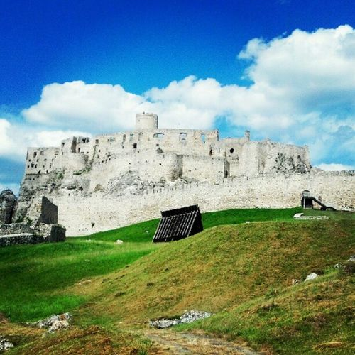 Castle on field against cloudy sky