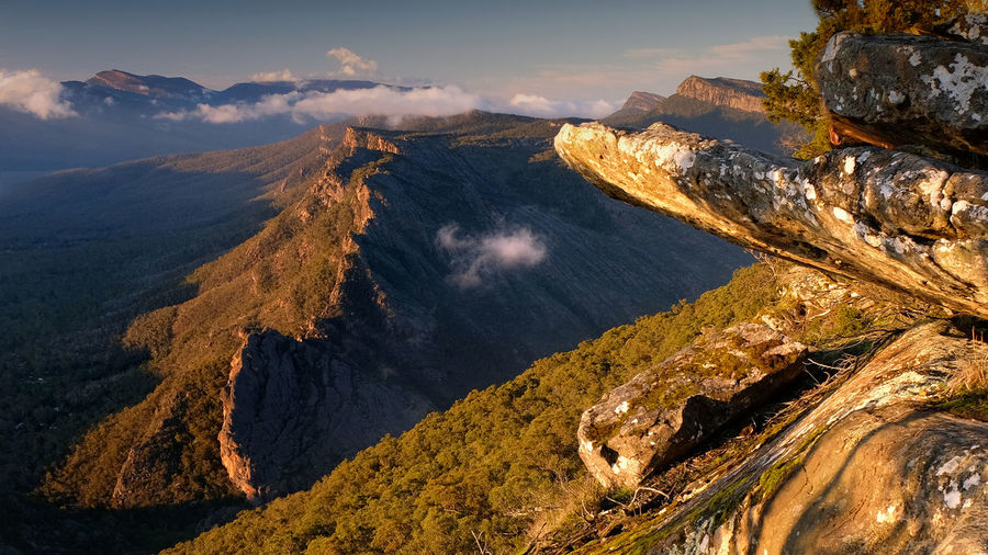 Mountain range and close up rocks at sunrise with clouds at the grampians