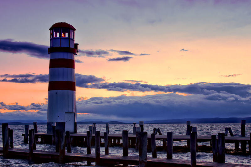 Lighthouse Architecture Beauty In Nature Building Exterior Cloud - Sky Light Tower No People Orange Color Sea Sky Sunset Tower Water Wood - Material Wooden Post