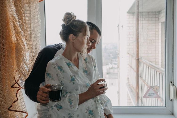 Woman looking away while sitting on window