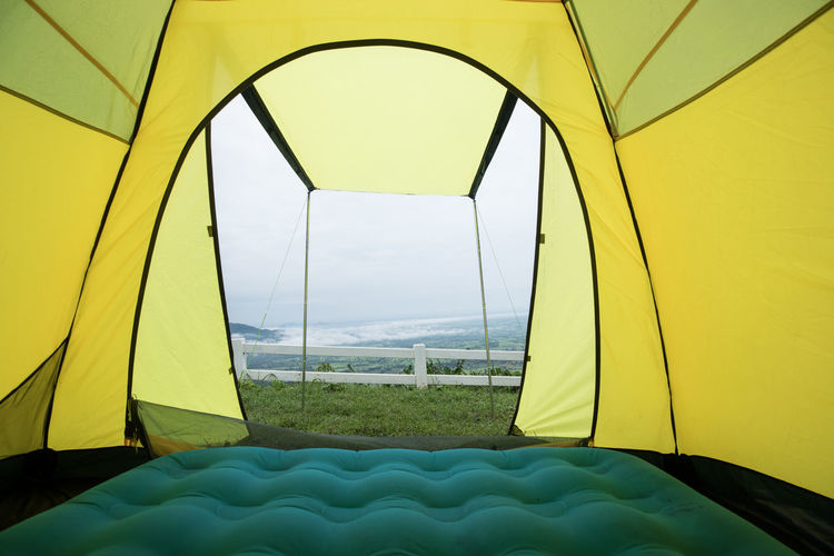 Close-up of tent on field seen through glass window