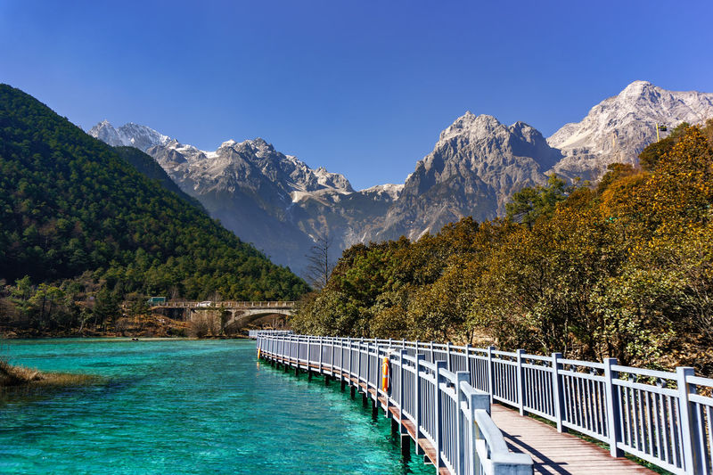 Jade Dragon Snow Mountain,Mount Yulong or Yulong Snow Mountain at Lijiang,Yunnan province,China. Beauty In Nature Blue Clear Sky Day Idyllic Mountain Mountain Range Nature No People Outdoors Railing Scenics Sky Sunlight Tranquil Scene Tranquility Travel Destinations Tree Water