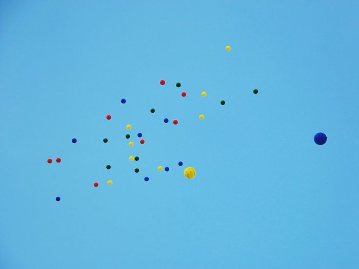 Low angle view of colorful balloons flying against clear blue sky
