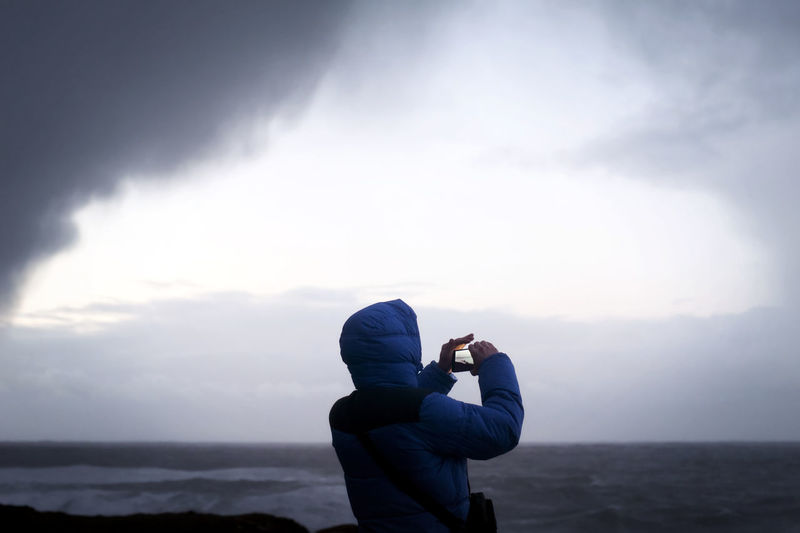 man takes a photo with mobile phone of sea storm Adult Adults Only Beauty In Nature Cloud - Sky Comunication Dangerous Day Leisure Activity Lifestyles Mobile Phone Mobile Photography Mobilephotography Nature One Man Only One Person Only Men Outdoors People Phone Photographer Scenics Sky Standing