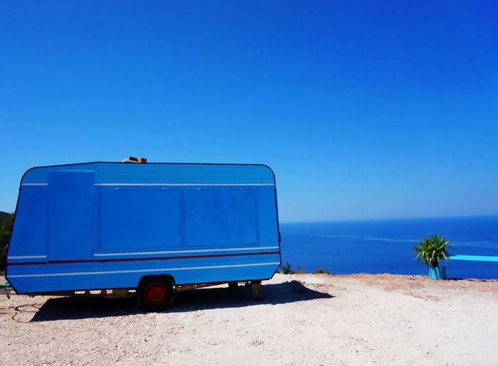 Blue Caravan On Field By Sea Against Sky