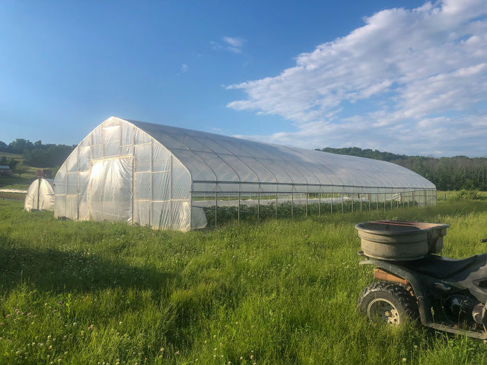 Scenic view of agricultural field against sky with greenhouse and off road vehicle