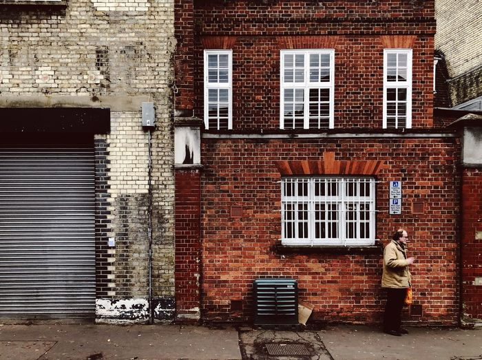 Man standing by window in front of building