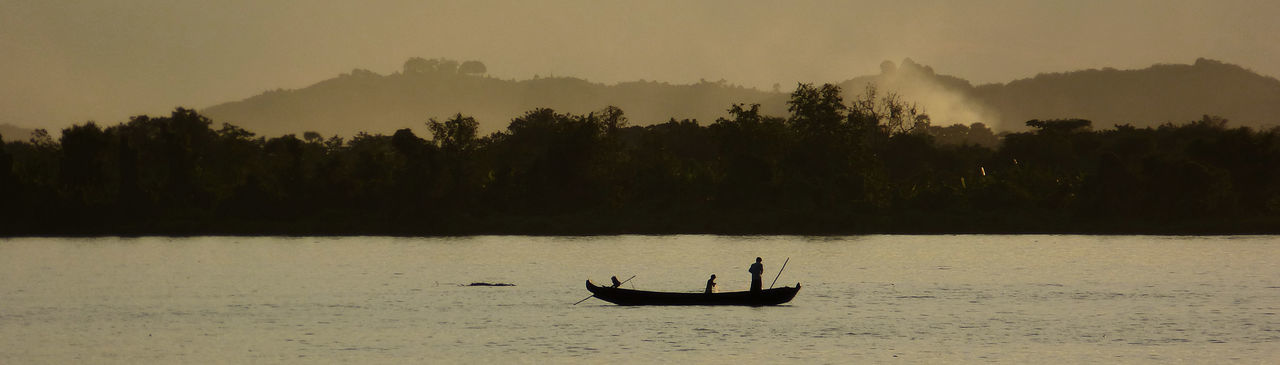 Silhouette man in boat on lake against sky