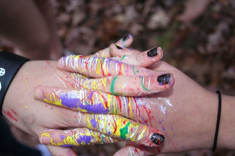 Cropped hands of women with paint