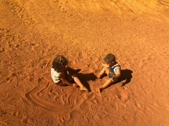 High angle view of siblings playing at sandy beach