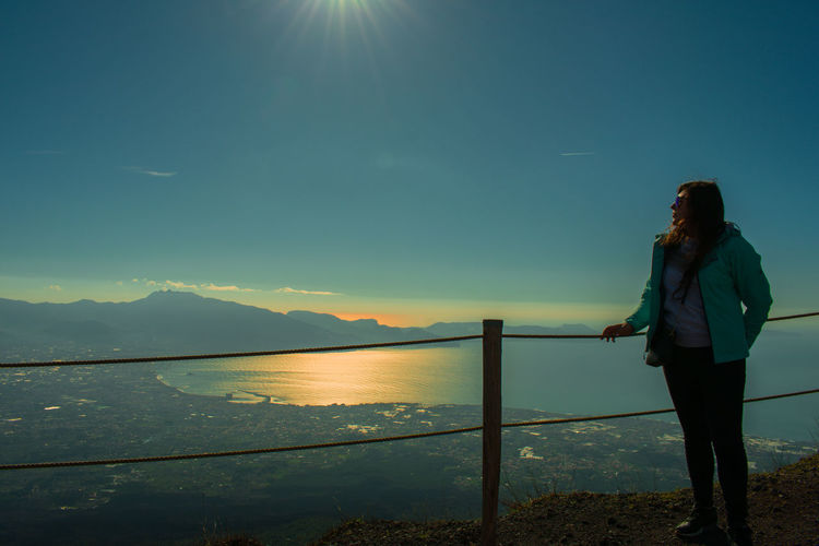 Mid adult woman standing on observation point against blue sky during sunset
