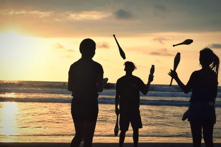 Friends Practicing Juggling Pins At Beach Against Sky During Sunset