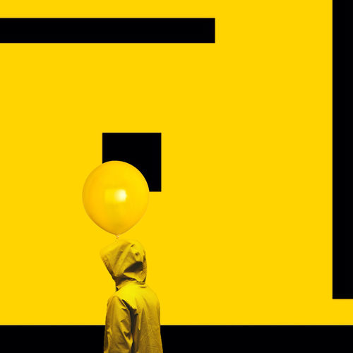 Person wearing yellow jacket with balloon standing by painted wall