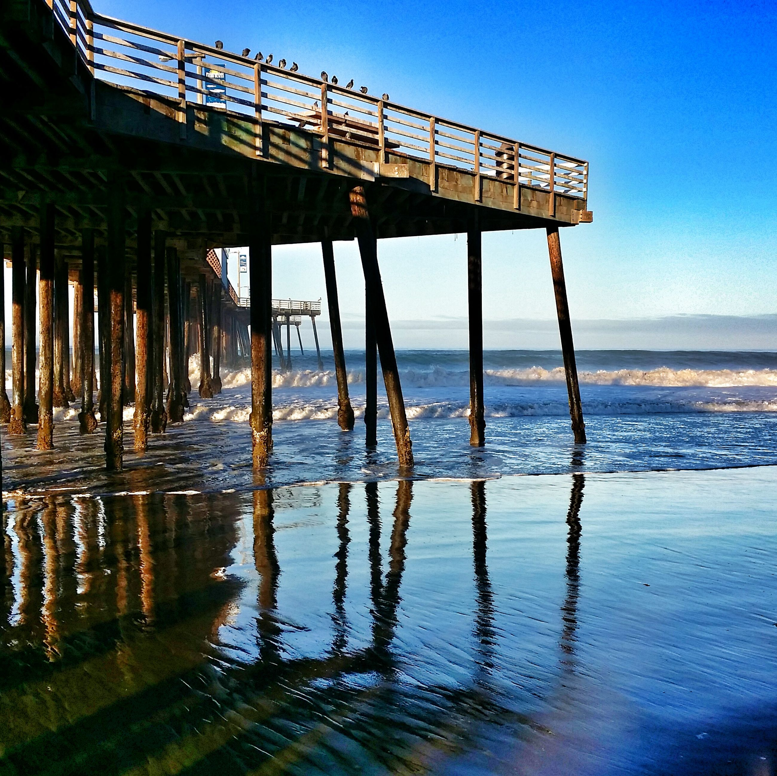 water, sea, beach, sky, horizon over water, pier, clear sky, tranquility, nature, tranquil scene, reflection, built structure, shore, sunlight, wood - material, day, outdoors, connection, rippled, no people