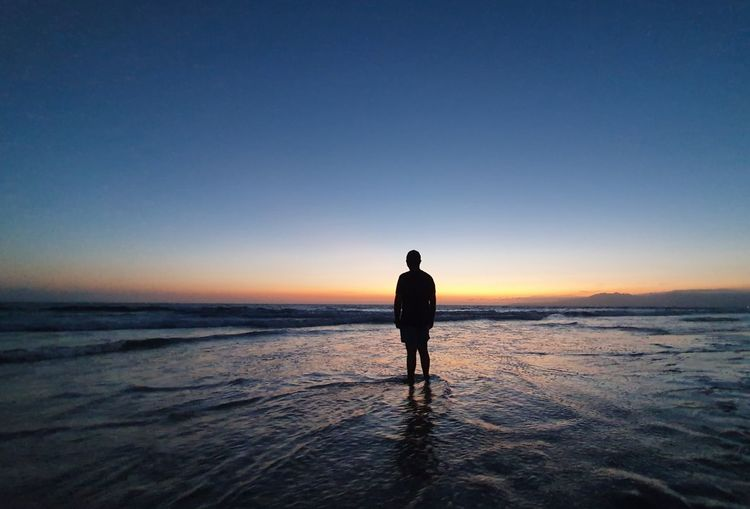 Rear view of silhouette man standing on beach against clear sky