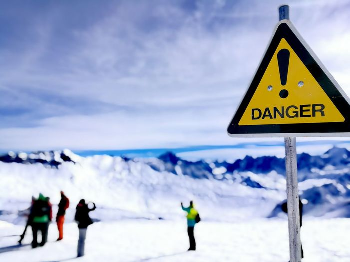 Danger sign against people on snowcapped mountain
