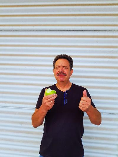 Portrait of smiling mature man having apple while standing against shutter