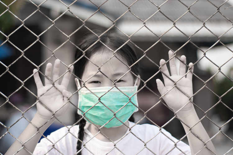 Close-up portrait of a girl seen through chainlink fence