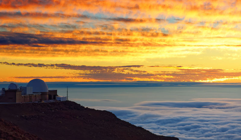 Full color sunset over a sea of clouds, foreground in shade, cloud pattern, research station at the edge of the picture - Location: Hawaii, Maui Island, Haleakala Volcano (Haleakalā) Evening Lights Beauty In Nature Built Structure Cloud - Sky Cloud Formations Clouds Sky Colorful Background Dark Foreground Dome Horizon Over Water Light Bulb Light Reflection Nature No People Orange Color Outdoors Scenics Sea Of clouds Sky Sunset Volcanic Landscape