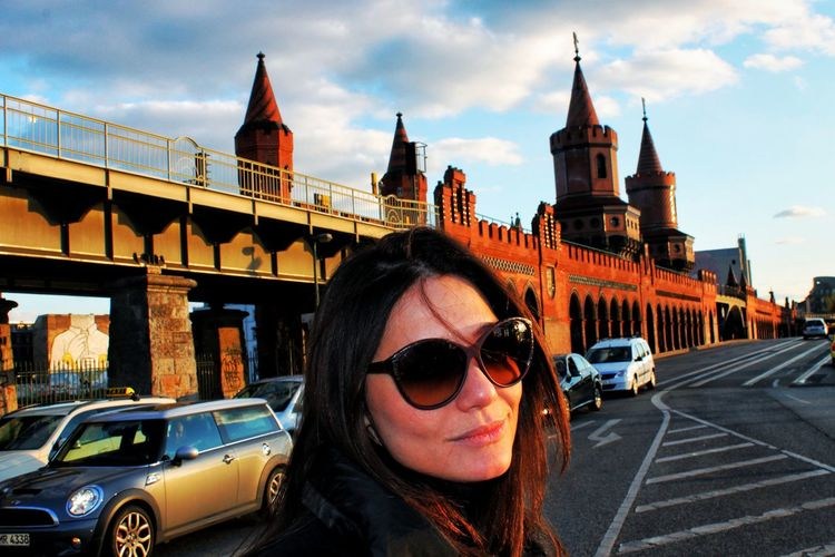 Young Woman Standing Against Oberbaum Bridge During Sunset