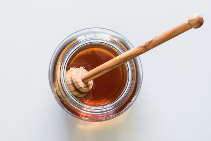 A jar of honey Isolated Close Up Close-up Condiment Food Honey Jar No People Stick Sweetener Top View Wand White Background