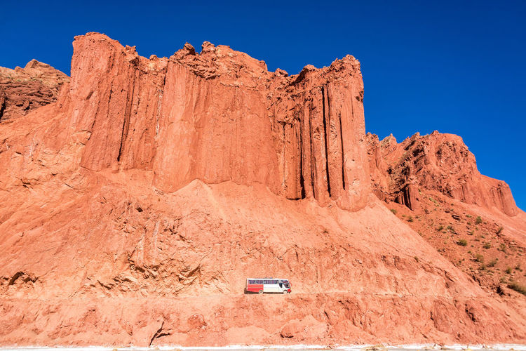 Bus passing by dramatic red cliffs near Tupiza, Bolivia Arid Arid Climate Beauty In Nature Bolivia Bus Cactus Canyon Cliff Countryside Desert Desert Formation Formations Landscape Red Rock Rocks Rugged Rural Sky South America Tourism Travel Travel Destinations TUPIZA