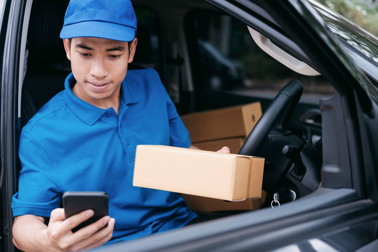 Delivery Man Holding Parcel While Sitting In Car