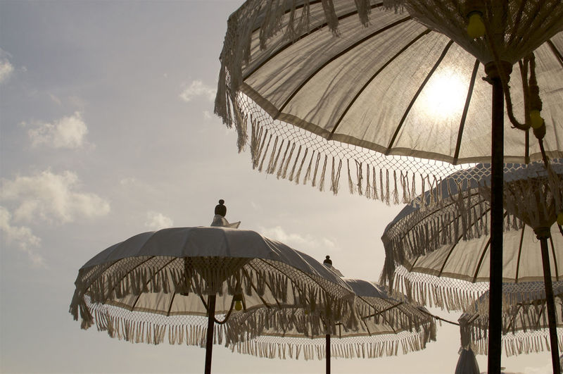 Picture of some beautiful white Balinese sun umbrella during sunset, decorated with yellow bulb lights and located at the famous Echo Beach in Canggu, Bali - Indonesia Umbrella Travel Bali Beautiful Religion Background Culture Balinese Sun Beach Traditional Decoration INDONESIA Exotic Blue Relax Art Ocean Holiday ASIA Tropical Summer Sea Yellow Hindu Sand Tradition Leisure Sunset Relaxation Color Sky Island Sun Bed Vacation Parasol Low Angle View Tourist Textile Asian  Decorate Coast Tourism Canggu Echo Beach White Silhouette Fringe Fringes