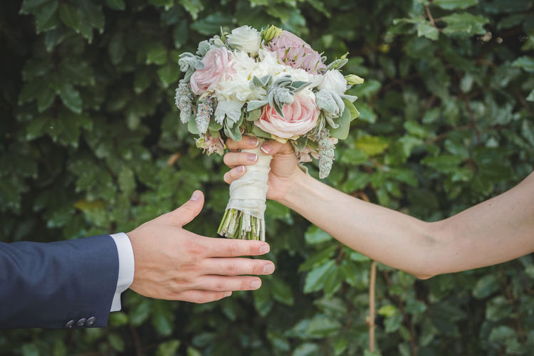 Cropped Hand Of Bride Giving Bouquet To Groom