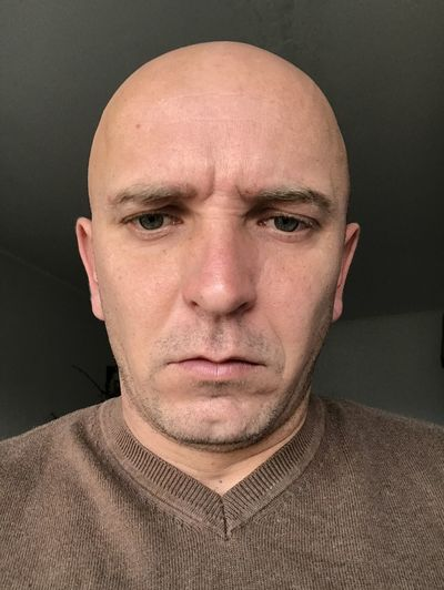 Close-up of bald man against at home