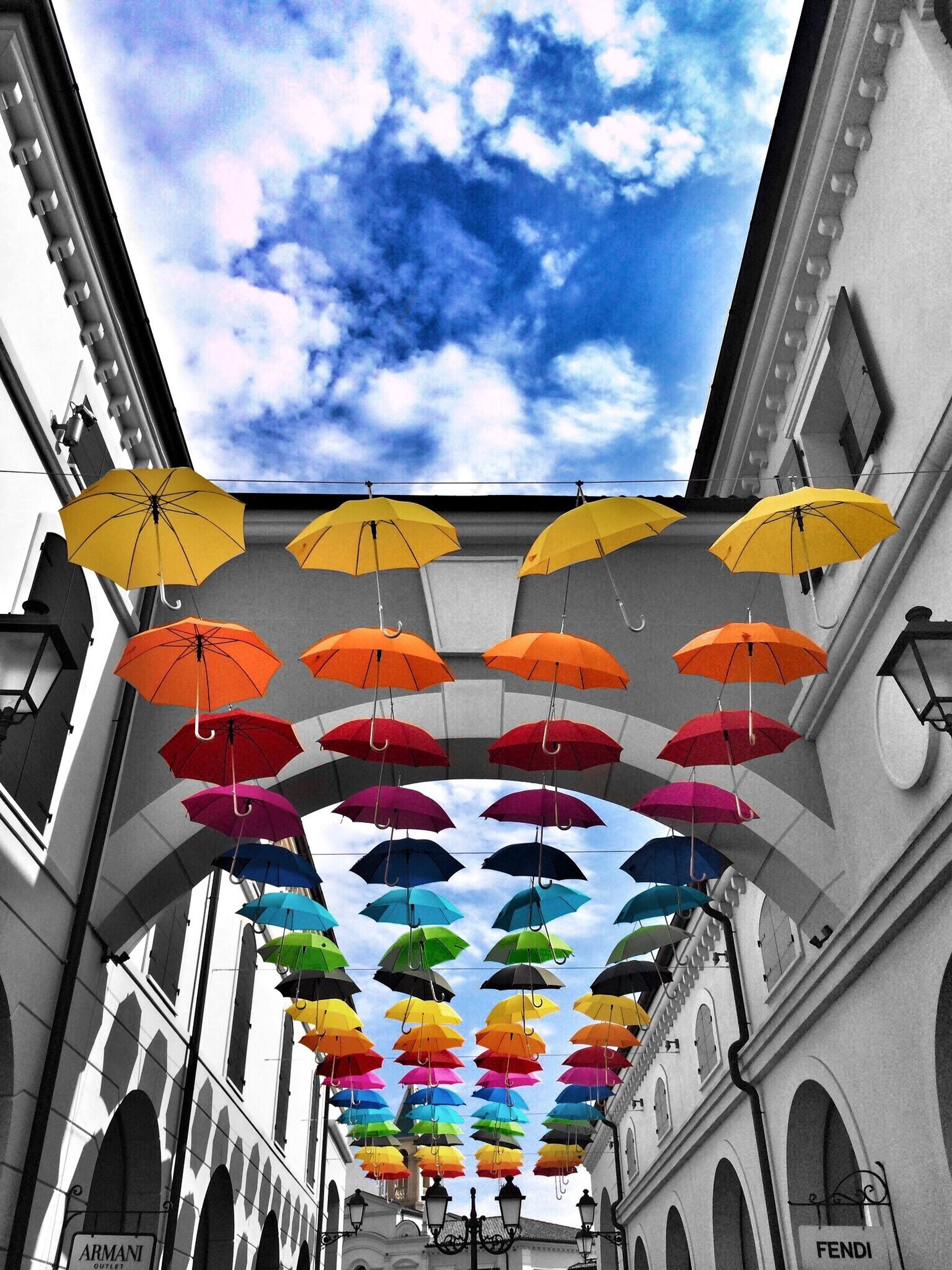 low angle view, multi colored, sky, architecture, built structure, building exterior, hanging, flag, colorful, cloud - sky, cloud, decoration, umbrella, variation, day, in a row, cloudy, parasol, balloon, art and craft