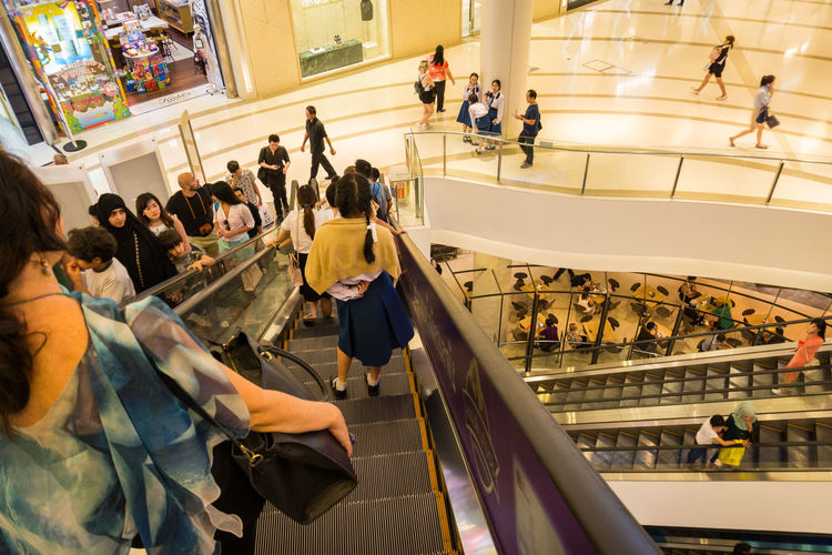 snap shot from escalator of people in Siam Paragon shopping mall, Bangkok, Thailand Bangkok Casual Clothing City Life Editorial  Escalator Group Of People Large Group Of People Leisure Activity Lifestyles Look Down Mixed Age Range Modern Person Shopping Mall SiamParagon Snap Photo