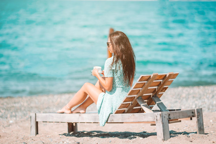 Woman sitting on bench in sea