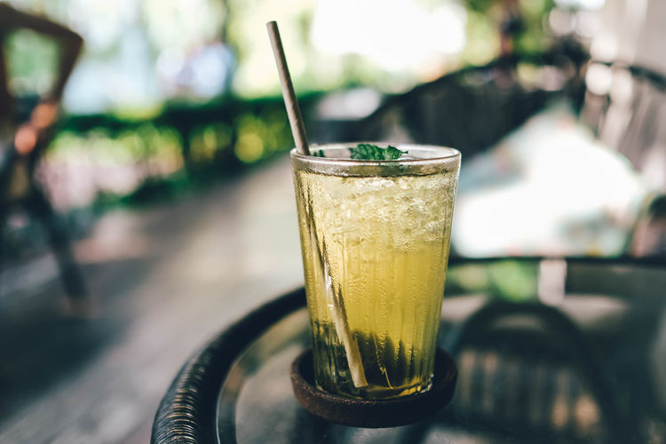 Iced green tea on the table with blurred background.