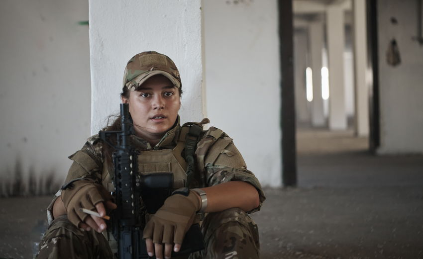 Portrait of soldier holding cigarette while sitting on floor