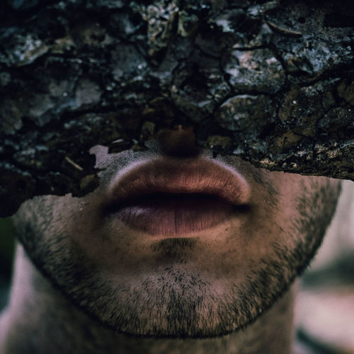 Close-up of man covering face with plant bark