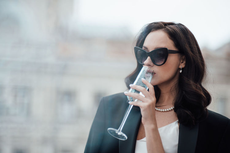 Portrait of a young woman drinking sunglasses