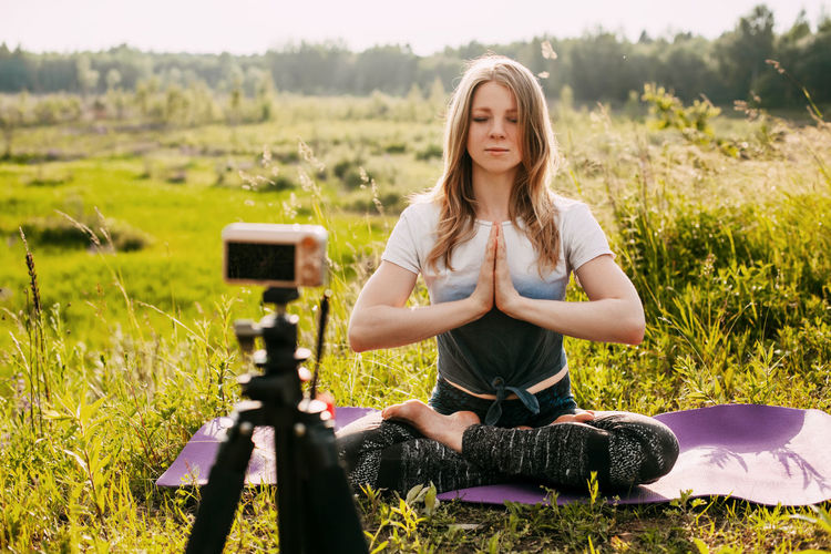 The girl practices yoga in nature and records a video lesson about yoga. yoga online