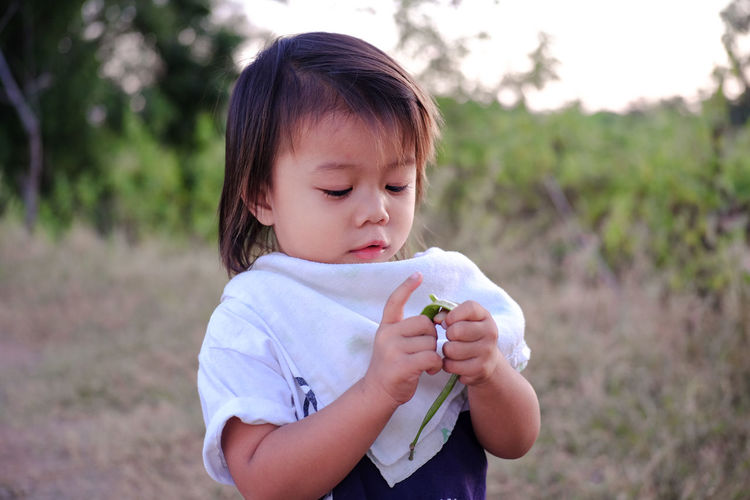 Girl eating green pea while standing on land