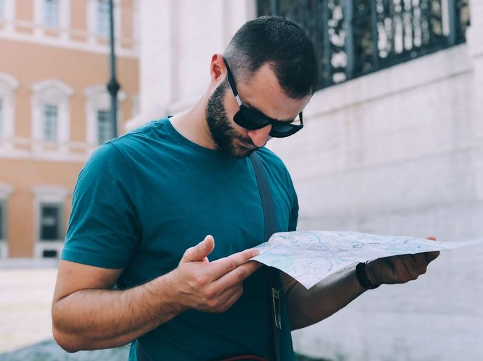 Mid adult man reading map while standing against buildings in city