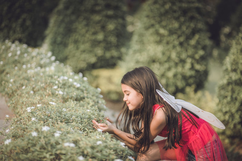 Side view of girl with costume wings crouching by plants in park