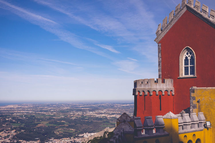The colourful Pena Palace of Sintra, Portual. Architecture Building Exterior Built Structure Building Sky Nature Cloud - Sky No People City Day Residential District Landscape Travel Destinations Blue Outdoors House Place Of Worship Travel Red Religion Sintra Palace Castle