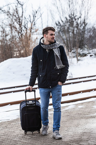 Young man in winter with suitcase Nature Travel Bare Tree Clothing Cold Temperature Day Front View Full Length Jeans Leisure Activity Lifestyles Looking Luggage Luggage Trolleys One Person Outdoors People Real People Snow Standing Tree Warm Clothing Winter Young Adult Young Men