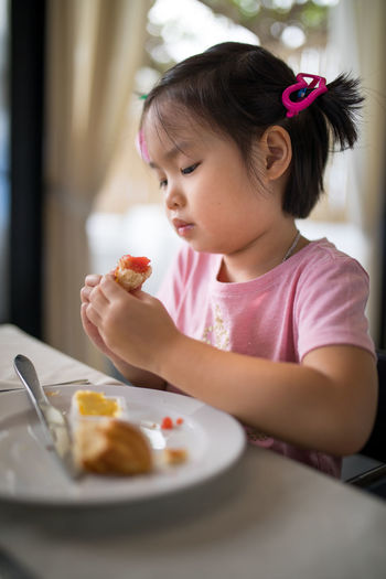Close-Up Of Cute Girl Eating Food At Table