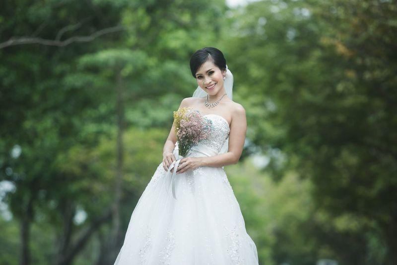 Portrait of smiling bride holding bouquet against trees