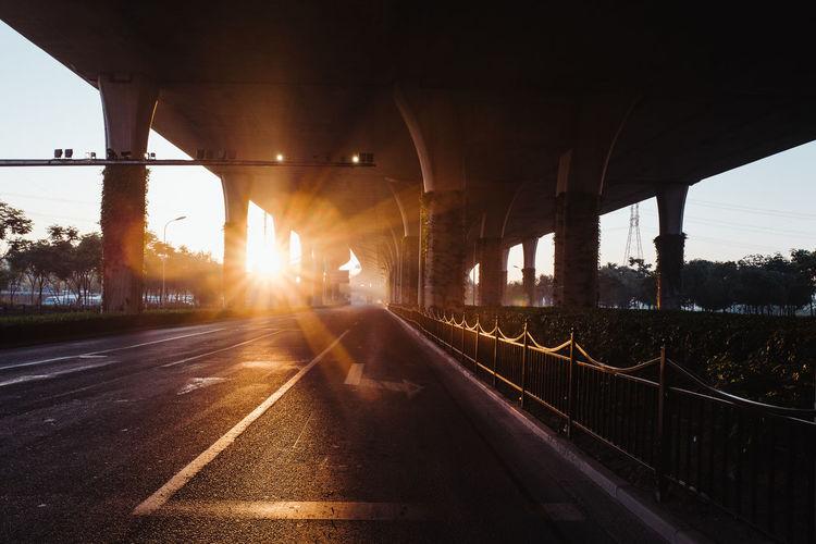 Bridge over highway against sky during sunset