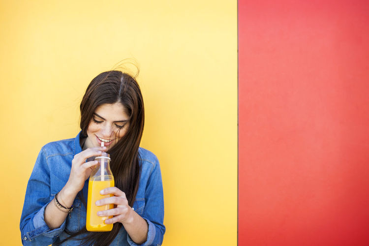 Young woman drinking glass against yellow wall
