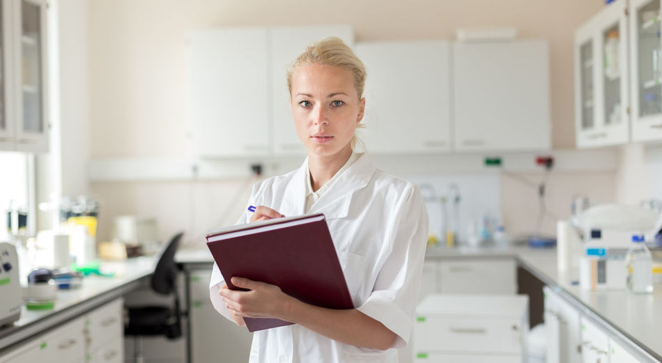 Portrait of woman writing in book standing in laboratory